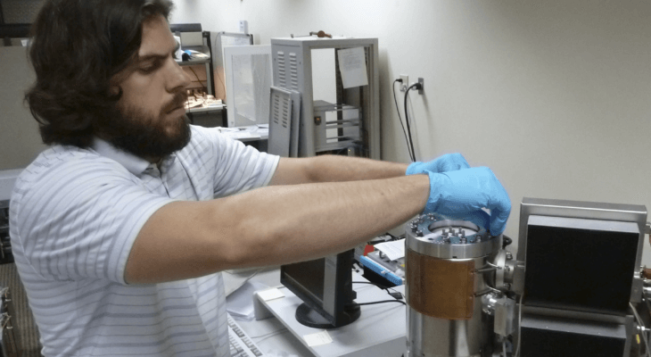 Alex Richards wearing gloves working in the lab